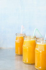 Three jars with freshly squeezed orange juice. Selective focus.