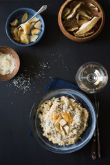 Dried porcini mushrooms risotto served with grated parmesan cheese and marinated porcini. Selective focus.