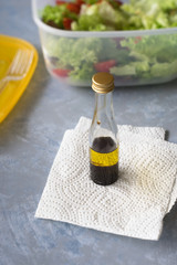 Small bottle with olive oil and balsamic vinegar to  season takeaway salad. Selective focus.