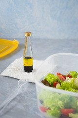 Prepared at home takeaway container with fresh lettuce and cherry tomatoes salad and small bottle with mix of olive oil and balsamic vinegar. Selective focus.