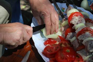 Man hands cutting onion near raw kebab