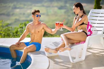 Young couple enjoying next swimming pool