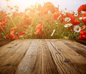 wooden rustic table of red poppies against sky with lig