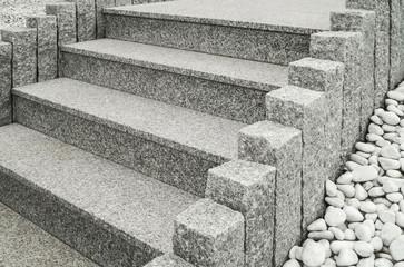 Closeup einer modernen Außentreppe aus Granit mit Stelen und Drainage aus großen weißen Kieselsteinen - Closeup of a modern exterior granite staircase with palisades and drainage of pebbles