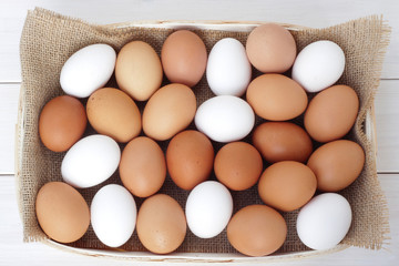 Brown and white chicken/hen eggs on wooden table