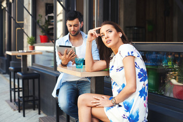 Bad date.  Man having fun with digital tablet during a date with
