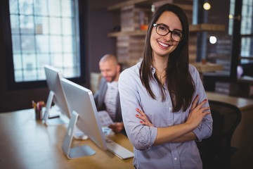 Businesswoman standing by desk while colleague in background