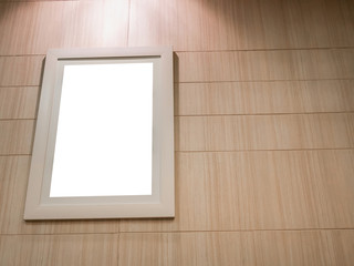 empty photo frame with light and wood wall