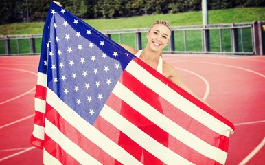 Composite image of female athlete holding american flag