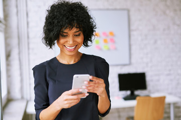 Attractive young woman using smartphone in trendy office Wall mural