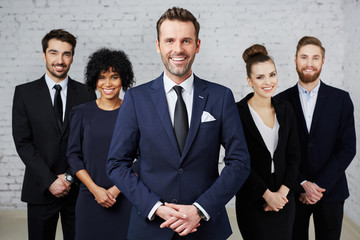 Group of businesspeople standing as a team with happy teamleader