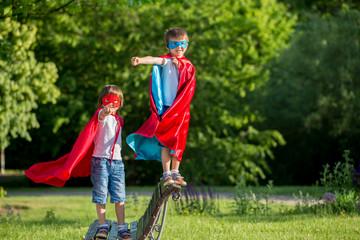 Two sweet little preschool children, boys, playing superhero in