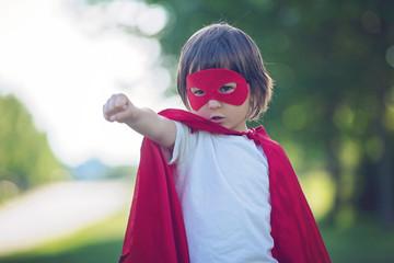 Sweet little preschool boy, playing superhero in the park
