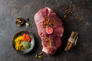 Raw Mutton meat with east spice on dark background.