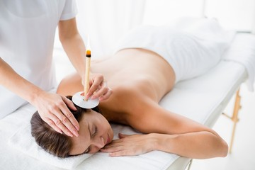 Naked woman receiving ear candle treatment from masseur