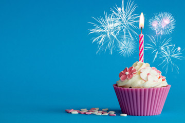 cupcake with burning candle and fireworks