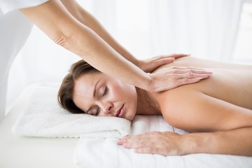 Masseur giving back massage to woman