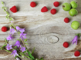 Decorative border, frame or background with summer colorful fruits and flowers on wooden plank. Natural decoration with red raspberries, green apples and violet bells flowers on wooden background.