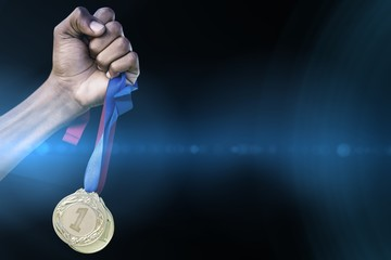 Hand holding two gold medals