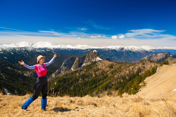 A woman in mountain day summer. Rocky route. Blue sky. Snow and