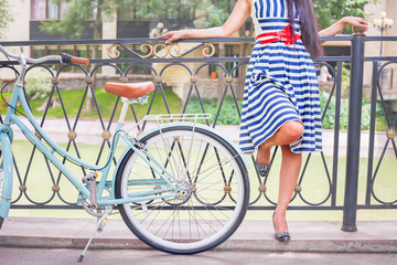 Young girl standing near fence near vintage bike at park