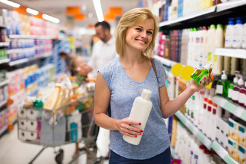 woman picking bottle with shampoo from shelf in cosmetics sectio