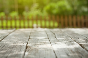 Garden wooden table with green bokeh