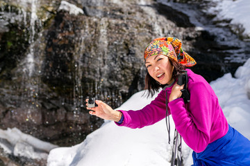 Woman hiker smiling and photographing waterfall.