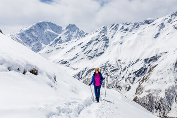 Hiker happy woman trekking on the snow in a snowy Caucasus mountains at spring