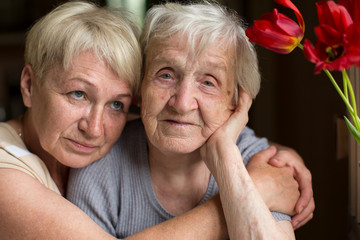 Mature woman hugging her old mother.