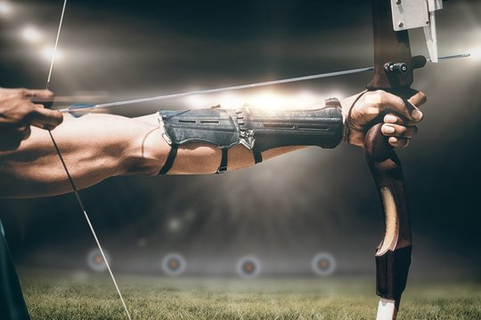 Composite image of close up of man stretching his bow