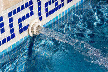 Detail view of a inflowing water jet into a swimming pool with blue tiles