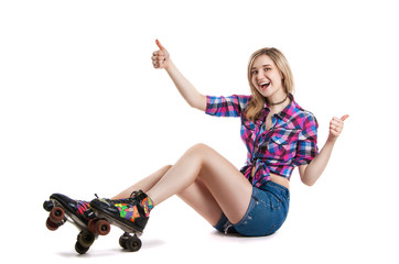 Joyful young girl in roller skates. A girl sits on the floor and laughs. It shows the gesture class.