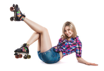 Cheerful young girl in roller skates. A girl sits on the floor and laughs. It shows the gesture class. A fall.