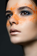 close-up portrait of a beautiful girl with paint around the eyes