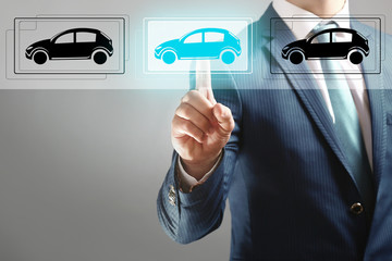 Businessman touching icon of car on virtual screen