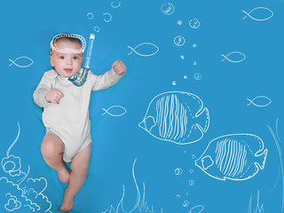 Lovely baby with painted mask and fishes on a blue background