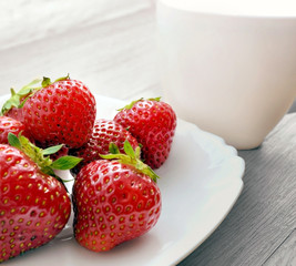 The photo ripe strawberries in a white plate with a cup