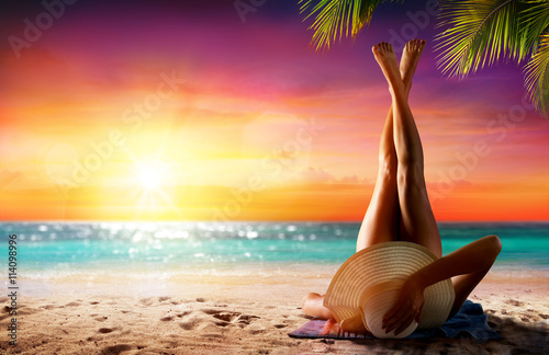Woman In Relaxation On Tropical Beach At Sunset