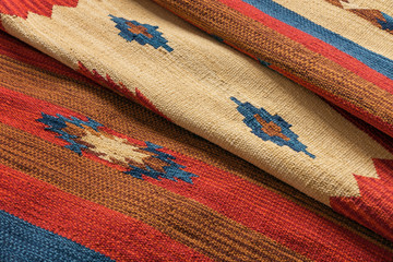 Close up of a hand woven striped patterned indian kilim carpet