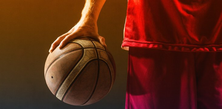 Close up on a basketball held by basketball player