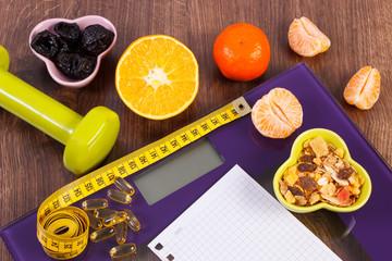 Digital scale with tape measure, tablets, dumbbells, fruits, muesli, slimming concept