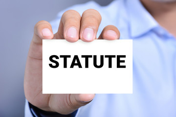 STATUTE word on the card shown by a man