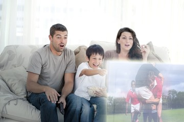 Composite image of happy family watching television
