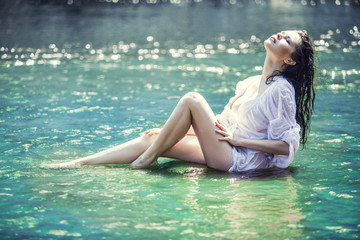 Young beautiful brunette woman enjoys the lake with  clear water