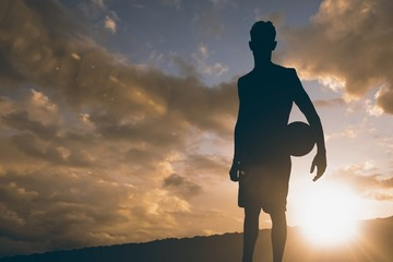 Composite image of sportsman holding a basketball