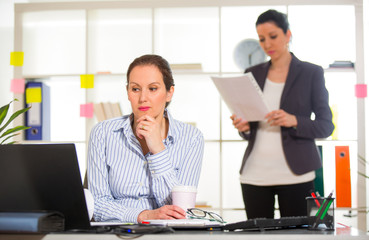 Businesswoman sitting at her desk with colleague on background