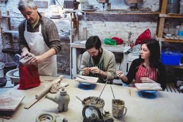 Mature potter working with colleagues at table