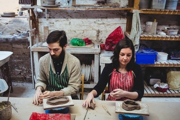 Male potter with female colleague working at table