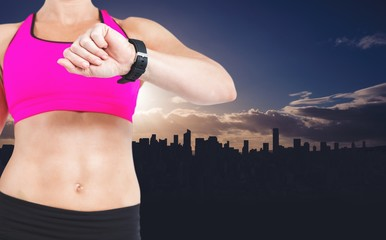 Composite image of female athlete watching her smart watch